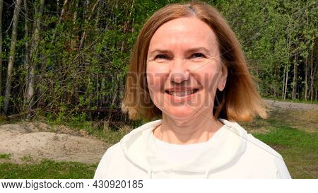 Charismatic Beautiful Mature Woman Face. Mid Adult Lady Smiling Outdoors. Portrait Of Female Age 55-