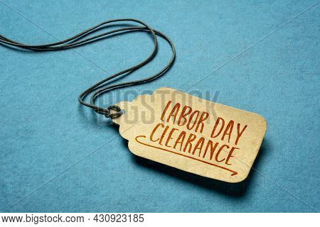 Labor Day clearance sign  - a paper price tag with a twine on blue background, sale and shopping concept