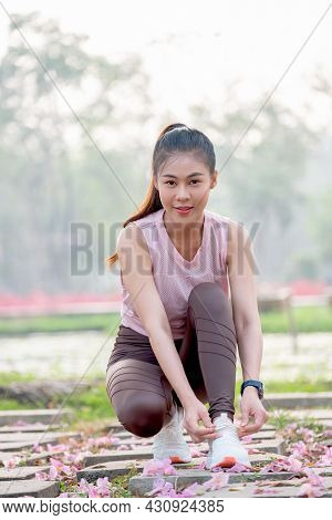 Asian Sport Woman Tie Shoelaces On Walkway With Flower On Floor In Part Or Garden Also Smile And Loo
