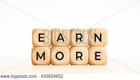 Earn More Phrase On Wooden Block Shape. Copy Space. White Background