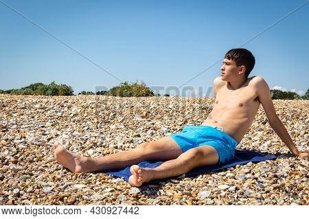 A 18 Year Old Caucasian Shirtless Teenage Boy Sunbathing On A Stoney Beach