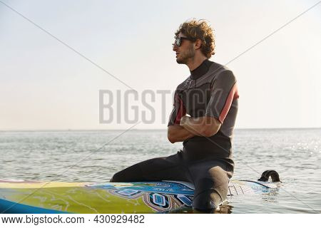 Young surfer with crossed arms sitting on surfboard in sea water. Thoughtful curly man wear diving suit and glasses. Concept of extreme water sport. Idea of summer vacation. Sunny daytime