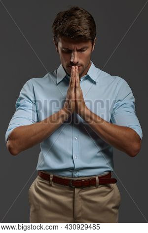 Young beautiful concentrated european businessman praying with closed eyes. Front view of bearded man with dark hair wear blue shirt. Concept of belief. Isolated on dark gray background. Studio shoot