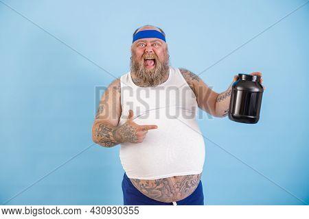 Joyful Obese Man Presents Large Bottle Of Nutrient Supplement On Light Blue Background