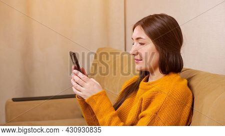 Smiling Brunette In Yellow Pullover Sits On Comfortable Sofa Of Brown Colour And Types On Black Smar