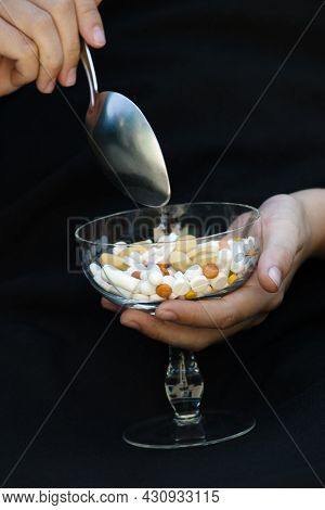 Taking Medication With A Tablespoon From A Glass