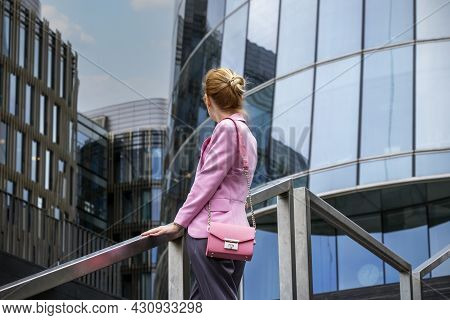 Young Woman With Strict Hairstyle In Pink Jacket Stands On Steps