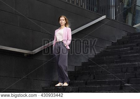 Young Serious Beautiful Blonde Millennial Woman With Long Hair In Pink Elegant Clothes Stands On Ste