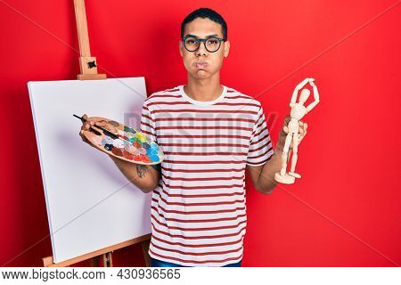 Young african american guy holding painter palette and art manikin puffing cheeks with funny face. mouth inflated with air, catching air.
