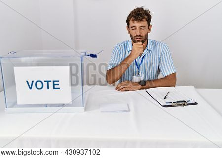 Young handsome man at political election sitting by ballot feeling unwell and coughing as symptom for cold or bronchitis. health care concept.