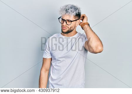 Young hispanic man with modern dyed hair wearing white t shirt and glasses confuse and wondering about question. uncertain with doubt, thinking with hand on head. pensive concept.