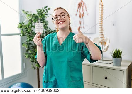 Young redhead physiotherapist woman holding prescription pills smiling happy and positive, thumb up doing excellent and approval sign