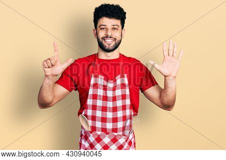 Young arab man with beard wearing cook apron showing and pointing up with fingers number seven while smiling confident and happy.