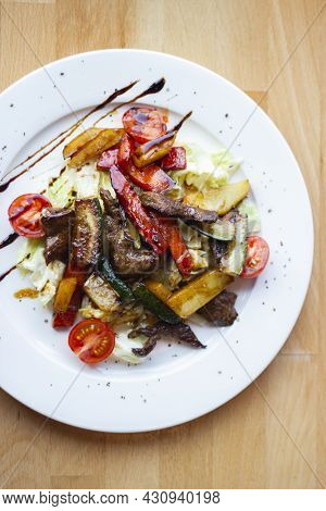 Delicious And Healthy Salad With Grilled Vegetables On A White Plate In A Restaurant