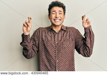 Handsome hispanic man wearing casual clothes gesturing finger crossed smiling with hope and eyes closed. luck and superstitious concept.