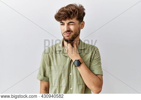 Young arab doctor man standing over isolated background touching painful neck, sore throat for flu, clod and infection