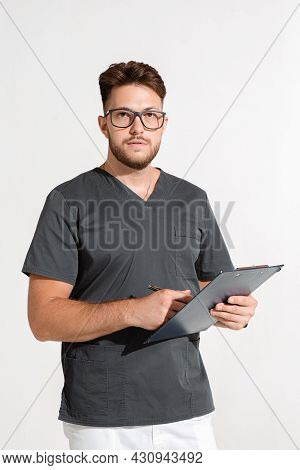 Professional Young Male Physician Practitioner In Glasses With Doctor Report, Prescribe Treatment On
