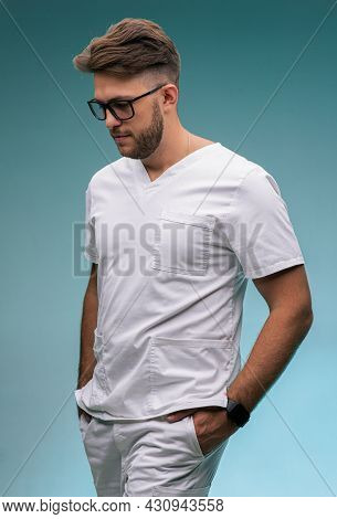 Handsome Successful Professional Young Male Physician Practitioner In Glasses, Medical Uniform On Bl