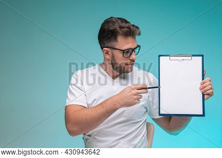 Professional Male Physician Pointing On Blank Space On White Paper Sheet. Doctor Report, Diagnosis,