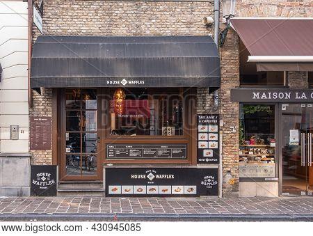 Brugge, Flanders, Belgium - August 4, 2021: Front Facade, Entrance Door And Dispaly Window Of World
