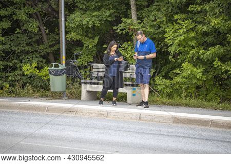 View Of Woman And Man Surfing On Mobiles Awaiting Buss On Public Buss Stop. Sweden. Uppsala. 08.23.2