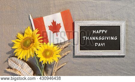 Happy Thanksgiving Text On Blackboard. Canada Flag With Sunflowers And Autumn Decorations. Flat Lay,