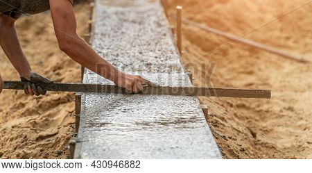 Worker Leveling Newly Poured Cement Into Formwork With Reinforcement, Building Foundation Of Residen