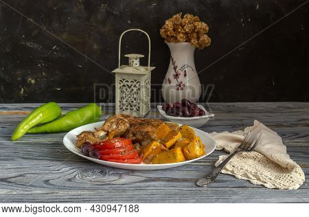 Stewed Chicken Leg, Sweet Potatoes (ipomoea Batatas), Tomatoes And Olives Lie On A White Plate On A