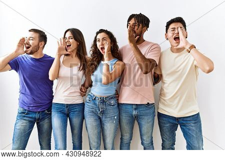 Group of young people standing together over isolated background shouting and screaming loud to side with hand on mouth. communication concept.