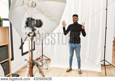 Young hispanic man with beard posing as model at photography studio showing and pointing up with fingers number seven while smiling confident and happy.