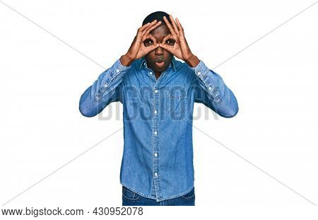 Young african american man wearing casual clothes doing ok gesture like binoculars sticking tongue out, eyes looking through fingers. crazy expression.