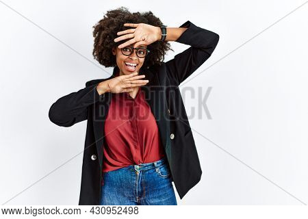 African american woman with afro hair wearing business jacket and glasses smiling cheerful playing peek a boo with hands showing face. surprised and exited