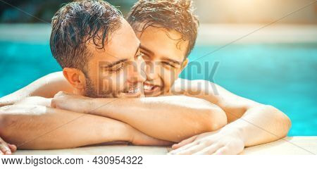 Gay couple relaxing in swimming pool. LGBT. Two young men enjoying nature outdoors, kissing and hugging. Young men romantic family in love. Happiness concept