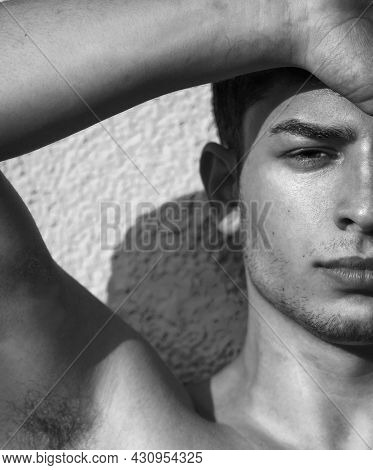 Young man fashion portrait. Handsome male close up. Black and white portrait of sexy muscular guy, looking at camera