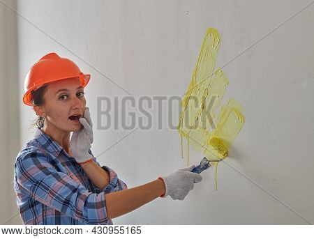 A Young Painter Paints The Wall Yellow With A Small Paint Roller