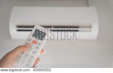 Hand Holding Remote Controller Directed On The Air Conditioner Inside The Room And Set At Ambient Te