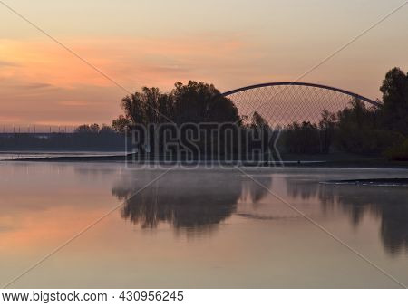 Bank Of The Ob At Dawn. Golden Cream Dawn, Haze Over The Calm Water Of The River, The Reflection Of
