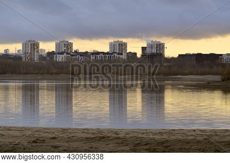 White Modern Homes. Autumn Sandy Bank Of The Ob River. Reflections In The Water. Yellow Sky On The H