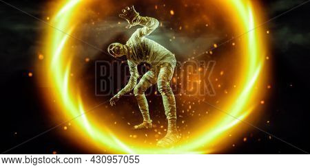 A sinister mummy in a fireball against the background of the Egyptian pyramids in the desert. Halloween. Ancient Egyptian mythology.