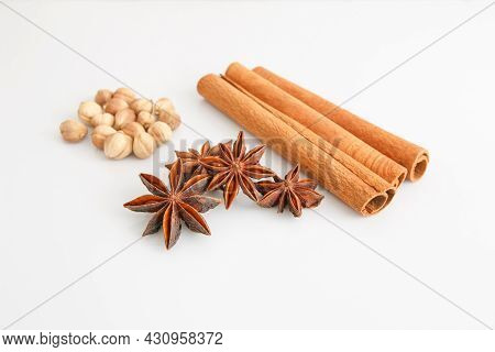 Anise Stars, Dry Cardamom, And Cinnamon Sticks On A White Background. Selective Focus