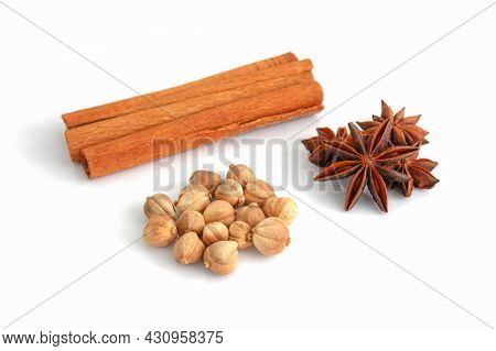 Dry Cardamom, Anise Stars, And Cinnamon Sticks On A White Background. Selective Focus
