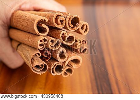 Close Up Shot Of Aromatic Dry Cinnamon Sticks On Hands With Wooden Table Background, Selective Focus