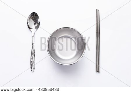 Small Aluminum Empty Bowls, Spoons, And Chopsticks On White Background. Top View