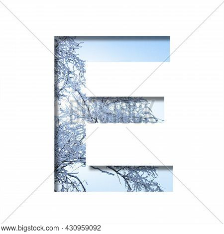 Winter Letters. The Letter E Cut Out Of Paper On The Background Of The Winter Sky And Snow-covered T