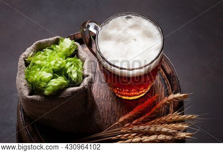 Lager beer mug, hops and wheat on old wooden barrel