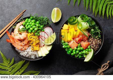 Poke bowls with shrimps, salmon, avocado and mango. Traditional hawaiian meal. Top view flat lay