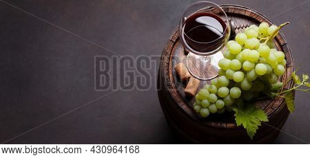 White grape, vintage corkscrew and red wine glass on old wooden wine barrel. With copy space