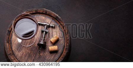 Vintage corkscrew and red wine glass on old wooden wine barrel. Top view flat lay with copy space