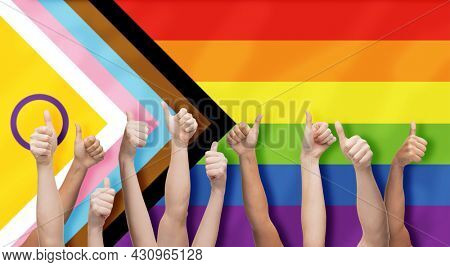 lgbtq, trans and intersex rights concept - multiracial human hands showing thumbs up over rainbow progress pride flag on background