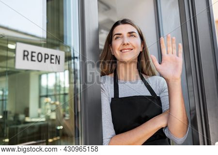 small business, reopening and service concept - happy smiling woman with reopen banner to window or door glass waving hand